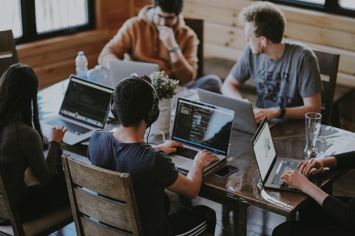 Um grupo de pessoas trabalhando com seus computadores em uma atividade de organização de documentos.