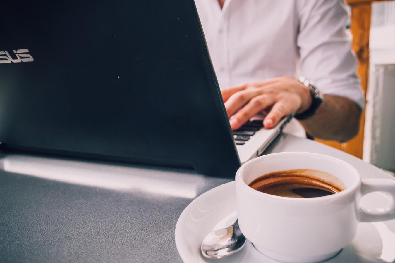 Um homem fazendo a consulta nfe completa em seu computador enquanto toma uma xícara de café.